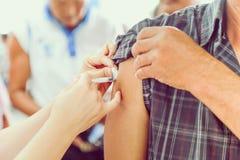 Skottet av människan räcker framställning av en injektion med en injektionsspruta Royaltyfri Foto