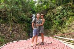 Skottet av tillgivet barn firar smekmånad par som tillsammans in står i förälskat anseende för rainforestpar nära en vattenfall Arkivbild