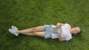 Skottet för den bästa sikten av den härliga le flickan som kopplar av med en bok på gräs på, parkerar arkivfilmer