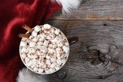 Skottet för den höga vinkeln av ett stort rånar av varm kakao med marshmallower på en lantlig trätabell arkivfoton