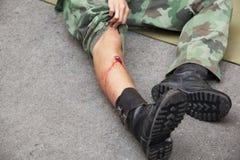 Skotthållsåret på soldat lägger benen på ryggen Arkivbild