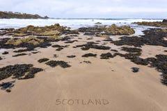 Skottland inskrev på våt gul sand för den steniga stranden Fotografering för Bildbyråer