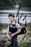 Skottland UK - Augusti, 2014 - ung man som är klädd i en traditionell skotsk tartan som spelar den säckpipe- skotten Fotografering för Bildbyråer