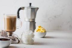 Skottsäkert kaffe Ketogenic keto bantar coffe som blandas med kokosnötolja och smör Kopp av skottsäkert kaffe och arkivfoton