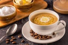 Skottsäkert kaffe som blandas med organiskt smör och MCT-kokosnöten arkivfoto