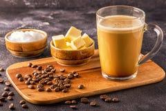 Skottsäkert kaffe som blandas med organiskt smör och MCT-kokosnöten arkivbilder