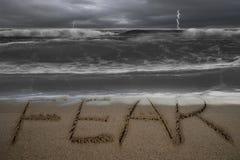Skräckordhand som är skriftlig på sandstranden med det stormiga havet Royaltyfri Fotografi