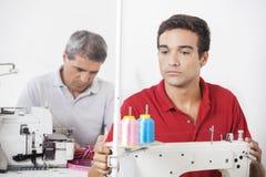 Skräddare Adjusting Sewing Machine i fabrik royaltyfri foto