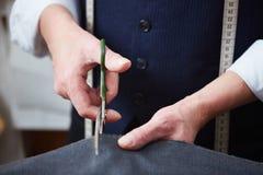 Skräddare Cutting Cloth i Atelier arkivbilder