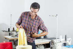 Skräddare Cutting Yellow Fabric på sömnadfabriken royaltyfria foton
