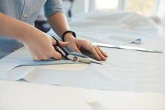 Skräddare Hands Cutting Material med sax på tabellen royaltyfri fotografi