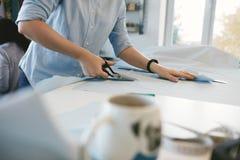 Skräddare Hands Cutting Material med sax på tabellen arkivbilder