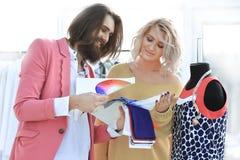 Skräddare och formgivare som diskuterar nya bekläda modeller royaltyfri fotografi