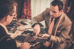 Skräddare och klient som väljer material för dräkt Royaltyfri Foto