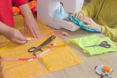 Skräddare som gör ett plagg i arbetsplats Processar av sömnaden på symaskinen syr symaskinen för händer för kvinna` s Royaltyfri Bild