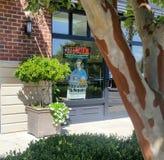 Skräddare Storefront med trädet och inlagda buskar Arkivfoto
