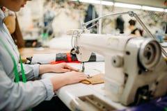 Skräddarehänder syr tyger på en symaskin royaltyfri foto