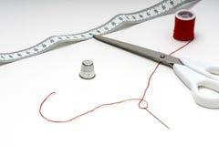 Skräddarehjälpmedel på den vita tabellen med den röda tråden Arkivfoto