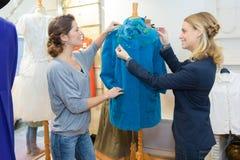 Skräddarekvinnor som arbetar med klänningen i studio royaltyfria foton