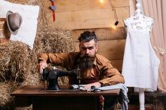 Skräddaremannen syr kläder Arkivfoto