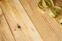 Skräddaremeterband på träbakgrund Royaltyfri Fotografi