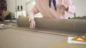 Skräddaren gör en modell med krita på materialet genom att använda en linjal stock video