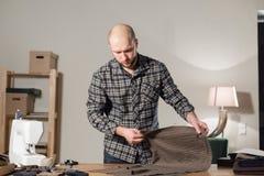 Skräddaren lägger ut ulltyget på den bitande tabellen Arbete för ung man som en skräddare och använda en symaskin in royaltyfri bild