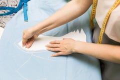 Skräddaren shoppar händer som rymmer måttseamstressarbete Markera och klippa tyg fotografering för bildbyråer