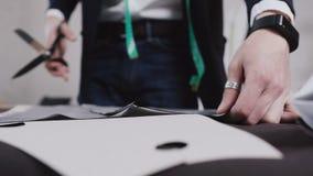 Skräddaren som klipps av en strimla av grått tyg med yrkesmässig sax Sömmerska Cutting Fabric lager videofilmer