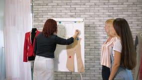 Skräddaren undervisar studenter att sy kläder på att klippa och att sy kurser i seminarium stock video