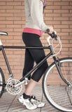 Skräddarsy fixiecykel och kvinna över tegelstenväggen Arkivfoto