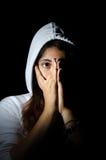 Skrämd flicka i huv på svart bakgrund Arkivfoto