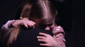 Skrämd flicka som kramar modern och gråter mot svart bakgrundsförskräckelse arkivfilmer