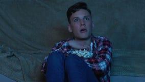Skrämd hållande ögonen på fasafilm för ung man hemma bara, skrämd person, natt lager videofilmer