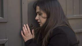 Skrämd kvinna som tigger till den öppna dörren som jagas av den tokiga mördaren, mordrisk, fasa arkivbild