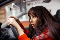 Skrämd kvinnlig chaufför i bil Arkivbild
