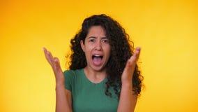 Skrämd latinamerikansk kvinna med lockigt hår i den gröna t-skjortan som är rädd av något och blickar in i kameran med stora ögon stock video