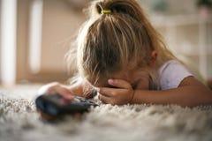 Skrämd liten flickakänsla, medan hålla ögonen på TV royaltyfria foton