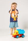 Skrämd pojke som spelar med den stora plast- bilen Arkivfoton