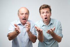 Skrämda två män har skrämt uttryck, blick nervöst som isoleras över vit bakgrund royaltyfri bild