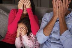 Skrämt latinamerikanskt familjsammanträde på Sofa And Watching TV Arkivfoton