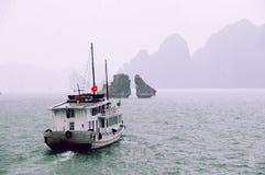 Skräpfartyg som seglar bort in i den regniga halongfjärden Vietnam för mist med land i bakgrunden arkivbilder