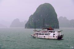 Skräpfartygsegling över den regniga halongfjärden Vietnam arkivbilder