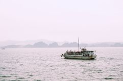 Skräpfartygsegling över den regniga halongfjärden Vietnam med land i bakgrunden royaltyfria foton