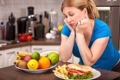 Skräpmat eller sund mat, begrepp av gravida kvinnan på en banta Royaltyfri Foto
