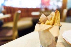 Skräpmat pommes frites som innehålls i rostfritt stålkoppen som förläggas på en tabell Restaurangplats och kopieringsutrymme Fotografering för Bildbyråer