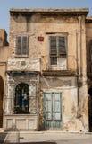 Skröpligt gammalt hus med en liten relikskrin framtill Fotografering för Bildbyråer