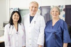 Säkra medicinska Team Smiling Together In Clinic Royaltyfri Fotografi