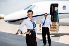 Säkra stewardesser som ler med piloten And Arkivbilder