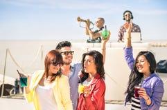 Skraj folk som tillsammans dansar musik och har gyckel på strandöversvallande beröm Fotografering för Bildbyråer